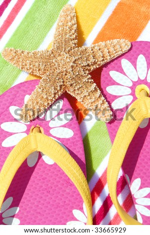 Starfish on pretty flipflops resting on beach towel - stock photo