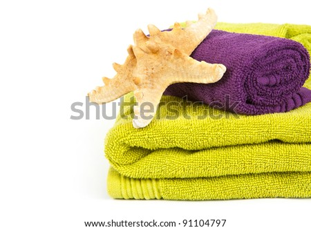 Starfish on stack of colorful towels on a white background - stock photo