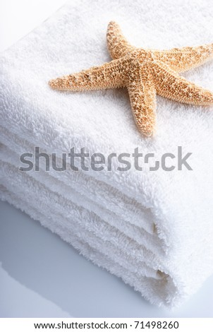 Starfish on stack of white towels with reflection. - stock photo