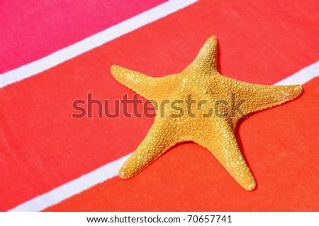 Starfish on striped beach towel - stock photo