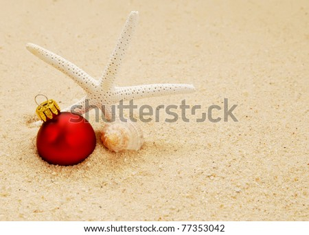 starfish with conch shell and red Christmas ornament on a beach - concept of a warm weather Christmas - stock photo