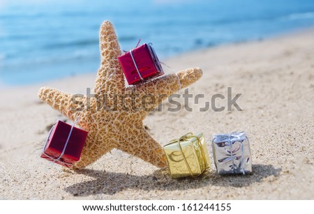 Starfish with few Christmas gift box on the sandy beach by the ocean - stock photo