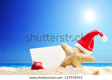 Starfish with Santa hat and a blank paper stuck on a beach on sunny summer day - stock photo