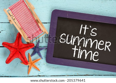 Starfishes and armchair on blue wooden background and small blackboard with text it's summer time - stock photo