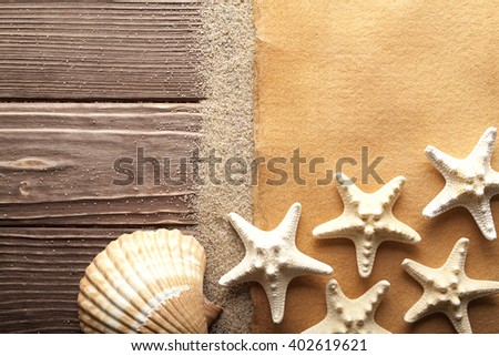 Starfishes and blank handmade paper sheet on wooden table - stock photo