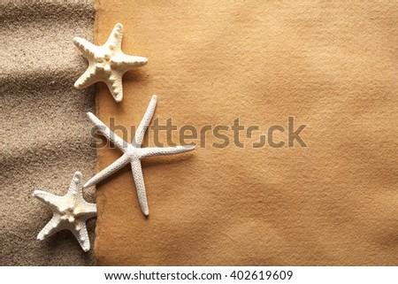 Starfishes and handmade paper sheet on beach - stock photo