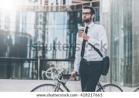 Staring new day with fresh coffee. Thoughtful young businessman holding cup of coffee and looking away while leaning at his bicycle with office building in the background - stock photo