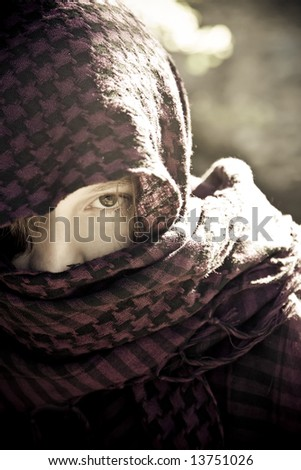 Staring woman portrait covered by violet veil - stock photo