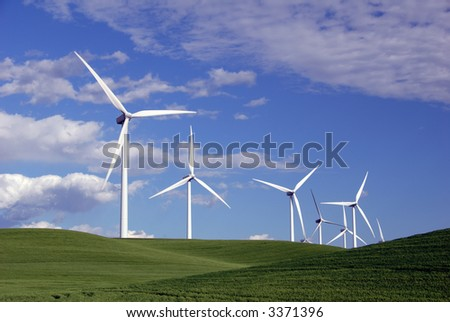 Stark White Electrical Power Generating Wind Turbines on Rolling Hills of Green Spring Wheat, Beneath Spring Clouds, Rio Vista, California