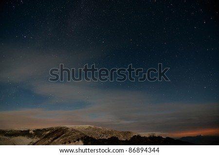 Starry cloudy sky in the mountains - stock photo