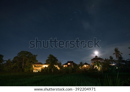 Starry night over the cottages and paddy fields in Ubud, Bali Island, Indonesia