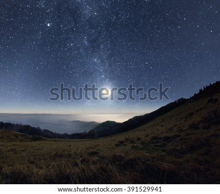 Starry night sky with rising full moon over the misty mountains - stock photo
