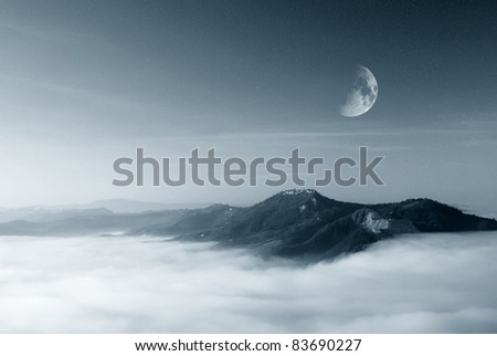 starry sky with moon over the foggy valley - stock photo