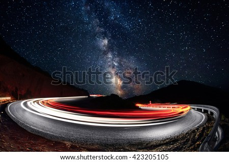 Stars and cars lights trails in the road - stock photo