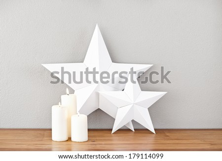 Stars and lit candles on a side board as deco - stock photo