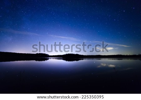 Stars and night clouds with reflections over the lake at night in Finland. - stock photo