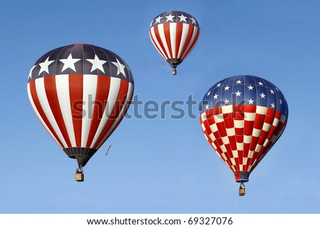 Stars and Stripes Hot Air Balloons Against a Bright Blue Sky - stock photo