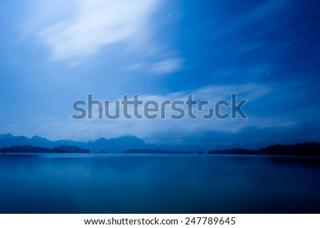 Stars in the blue sky. Below is the peaceful lake and reflection of mountains on water. - stock photo