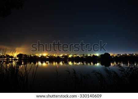 Stars in the night sky on a background city lighting. The bright lights reflected on the flat surface of the river. - stock photo