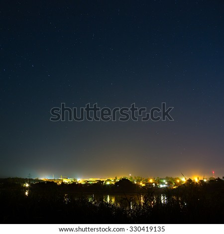 Stars in the night sky on a background city lighting. The bright lights reflected on the flat surface of the river.