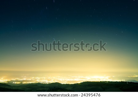 Stars raining over city at night. Long exposed picture. - stock photo