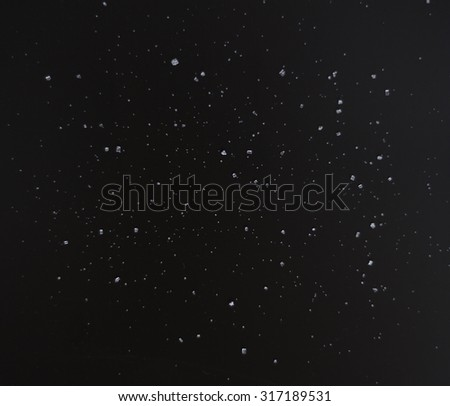 stars (salt and sugar) on a black background - stock photo