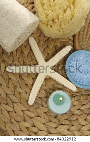 starshell and bowl of bath salt and candle on woven wicker mat - stock photo
