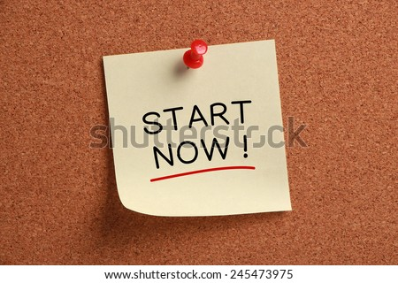 Start Now sticky note pinned on cork board. - stock photo