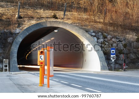 start of a conrete tunnel with fading lights of traffic and orange emergency telephone booth