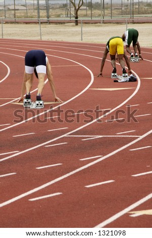 Start of the men's 400 meter run during a college track meet. - stock photo