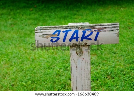 Start Sign New Beginning.  A weathered wooden start sign marks the beginning of something new. - stock photo