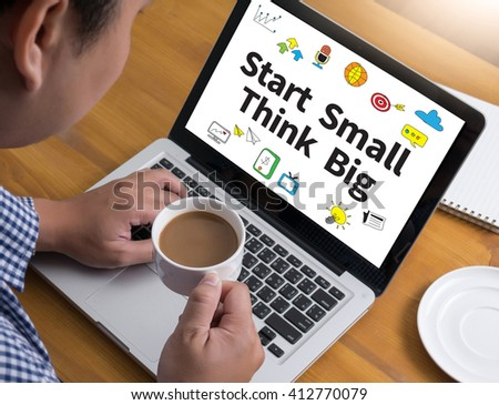 Start Small Think Big Businessman at work. Close-up top view of man working on laptop while sitting at the wooden desk , coffee - stock photo