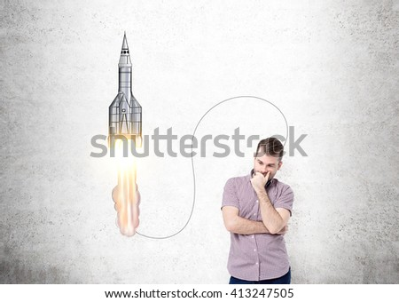 Start up concept with thinking caucasian guy standing against concrete wall with sketch - stock photo