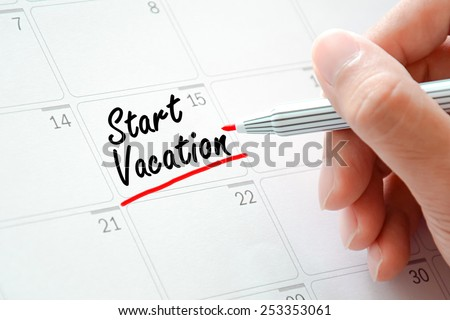 Start Vocation text on the calendar (or desk planner) underlined with red marker - stock photo