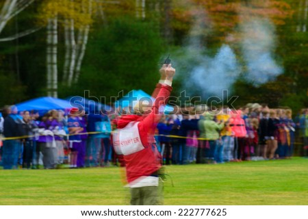 Starter firing his gun at the start of the of a cross country race. - stock photo