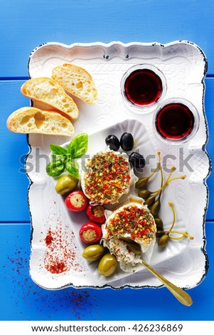 starter of green olives, black olives, capers, buffalo mozzarella, artichokes and red Chili peppers filled with tuna on blue - stock photo