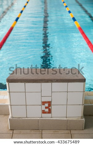 Starting blocks and lanes in a swimming pool. Edge of indoors sport swimming pool. Starting platforms with number 3 for swimming races and competitions. Sport and health concept - stock photo