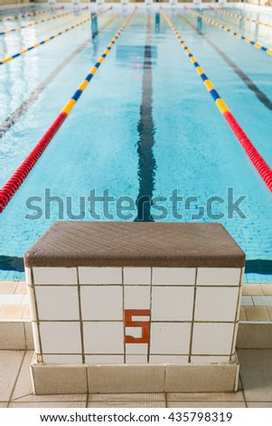 Starting blocks and lanes in a swimming pool. Edge of indoors sport swimming pool. Starting platforms with number 5 for swimming races and competitions. Sport and health concept - stock photo