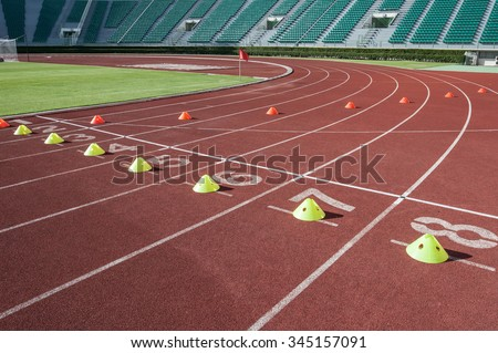 Starting blocks at the start in the lanes of running track, Red Asphalt for runners, Athletics Starting Blocks on a red running track in a stadium - stock photo