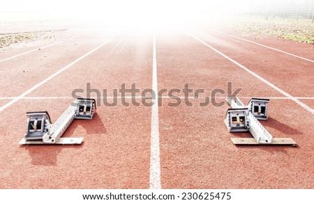 starting blocks on running tracks - stock photo