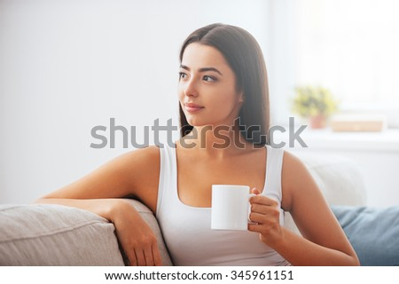 Starting day with cup of fresh coffee. Beautiful young woman holding coffee cup and looking thoughtful while sitting on the couch at home  - stock photo