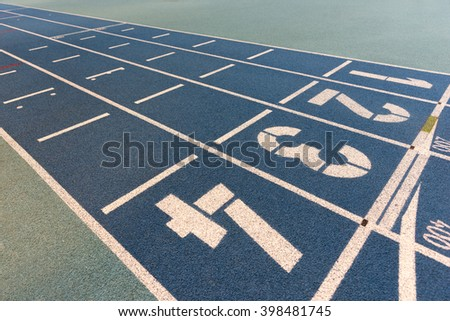 Starting line on blue indoor running rack for athletics - stock photo