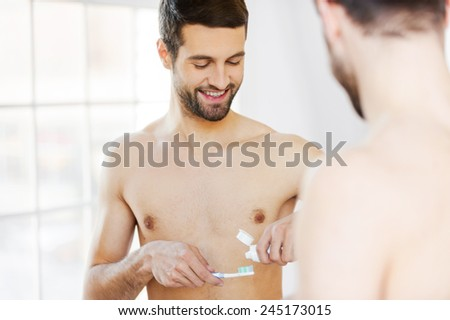 Starting new day with teeth brushing. Rear view of handsome young beard man preparing to brush his teeth while standing against a mirror - stock photo