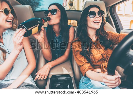 Starting new journey with champagne. Three beautiful young cheerful women looking at each other with smile and drinking champagne while sitting in car - stock photo