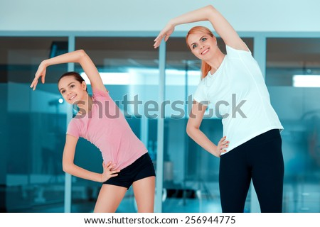 Starting the workout. Beautiful mature woman and her teenage daughter in sports clothing exercising aerobics against glass wall in the gym - stock photo