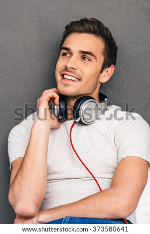 Starting weekends with good music. Cheerful young man adjusting his headphones and looking away with smile while sitting against grey background - stock photo