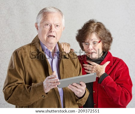 Startled man and woman looking at computer tablet - stock photo