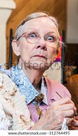 Startled old woman with crochet in livingroom - stock photo