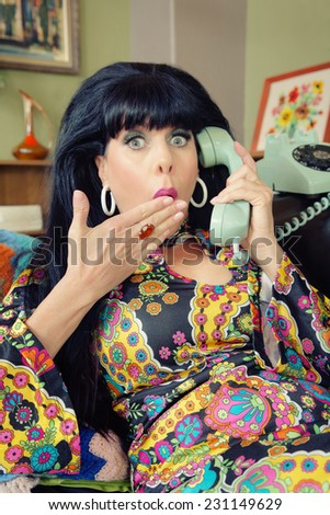 Startled woman in paisley dress on rotary telephone