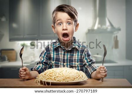 Startled yound boy with noodles